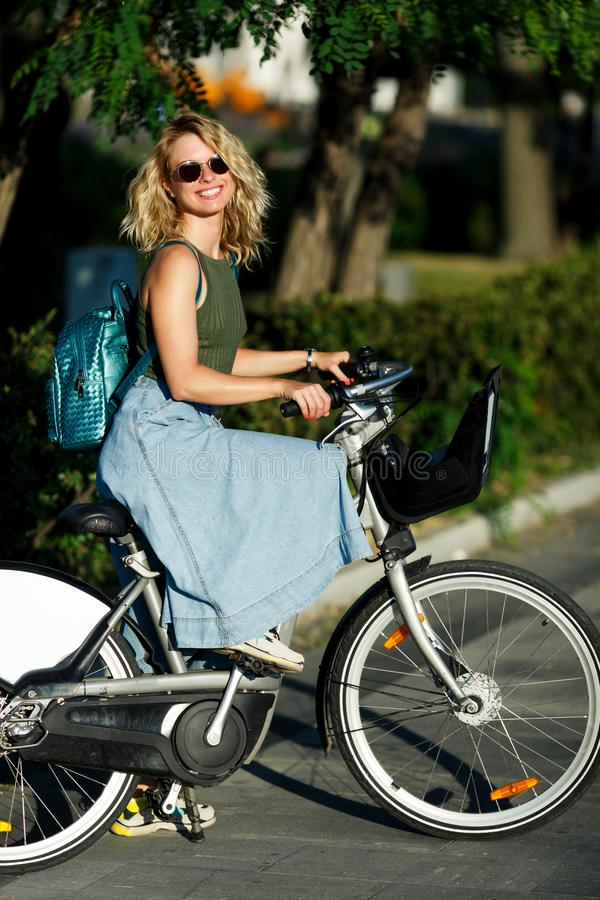 Photo of young blonde in sunglasses and long denim skirt standing next to bike near green bushes in city stock photography