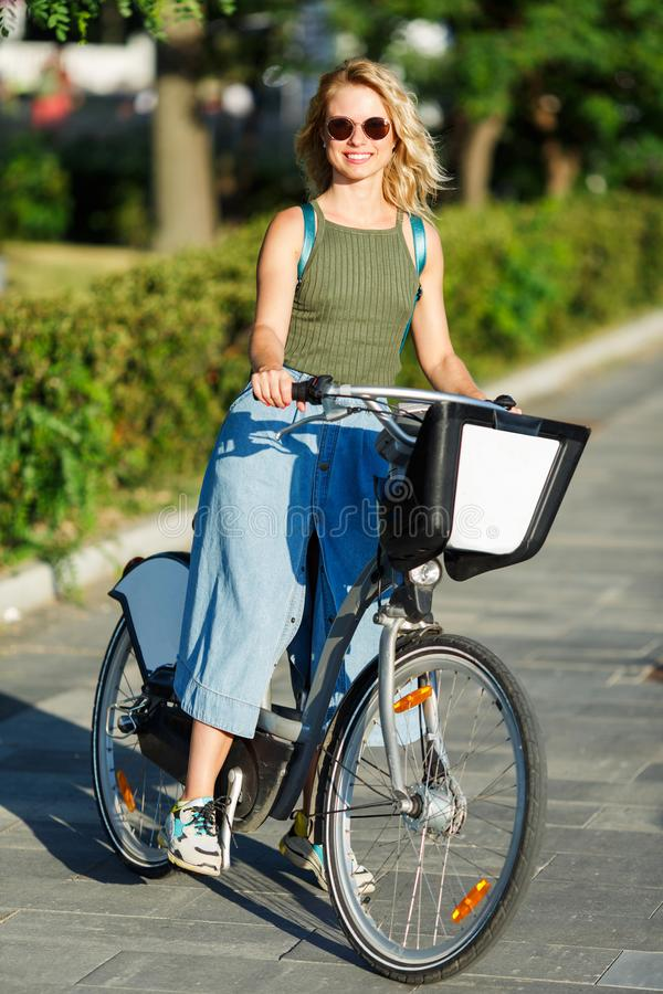 Photo of young blonde in sunglasses and long denim skirt standing next to bike on road in city royalty free stock photos