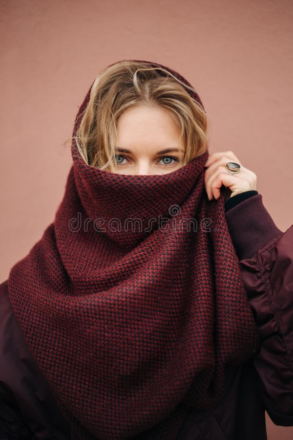 Photo of young blonde woman with closed scarf face on background of wall. royalty free stock images