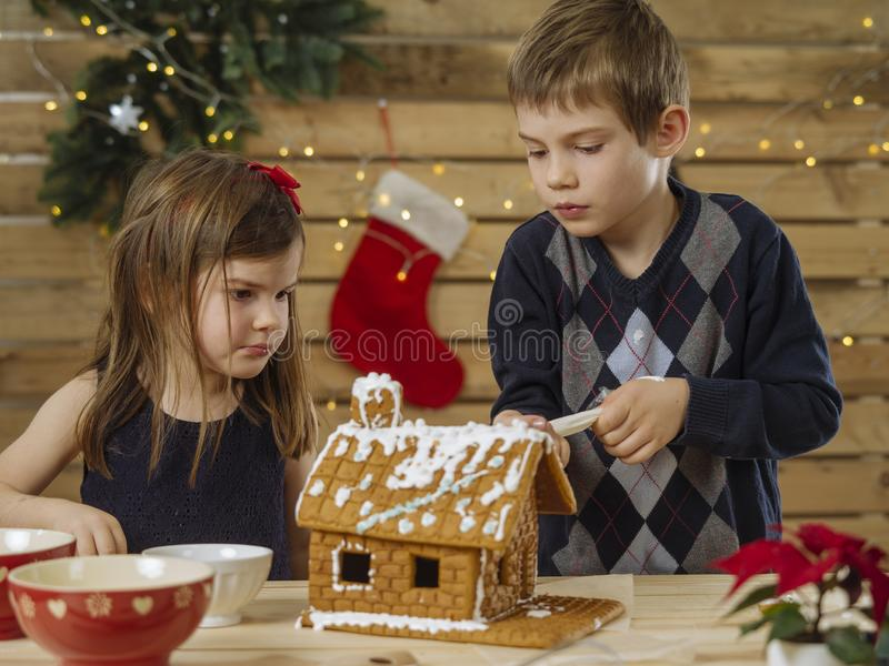 Brother and sister decorating gingerbread house stock photos