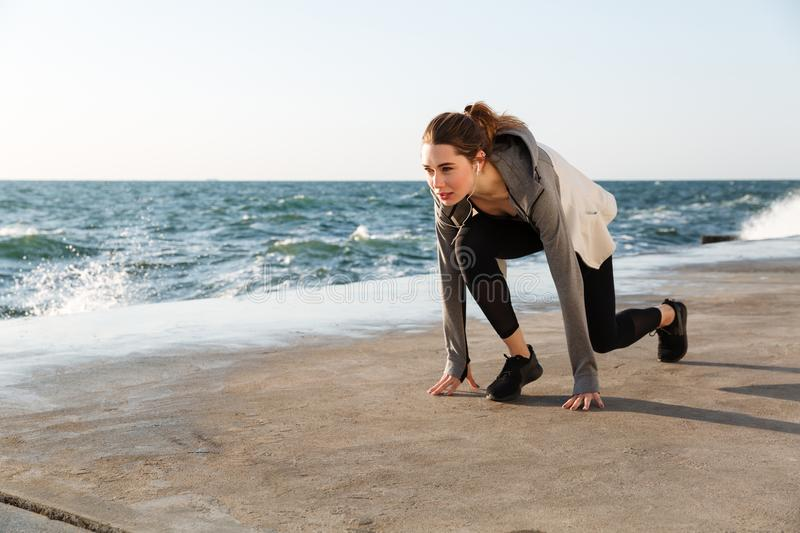 Photo of young brunette sport woman preparing to run, seaside outdoor stock photos