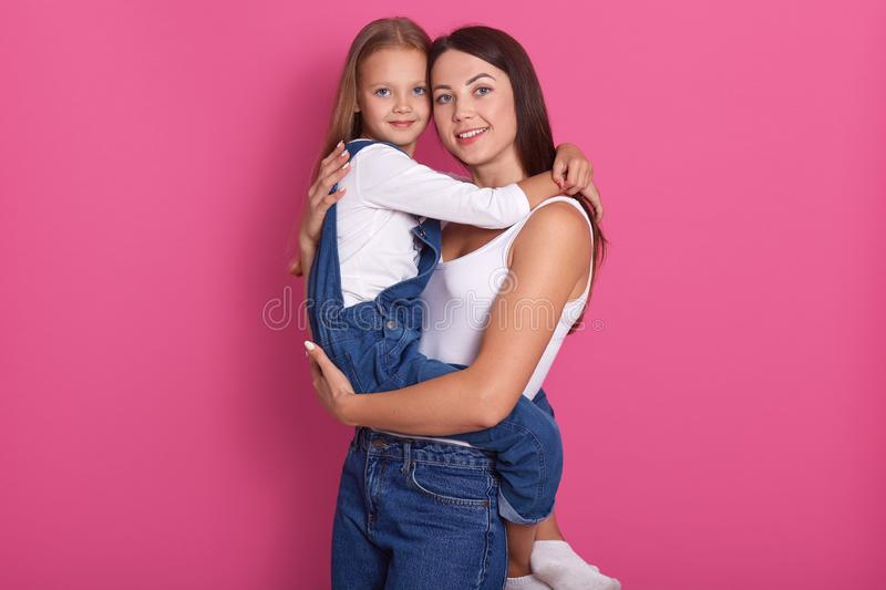 Photo of young charming mother with her little daughter embracing and smiling isolated over pink background, wearing casual outfit royalty free stock photos