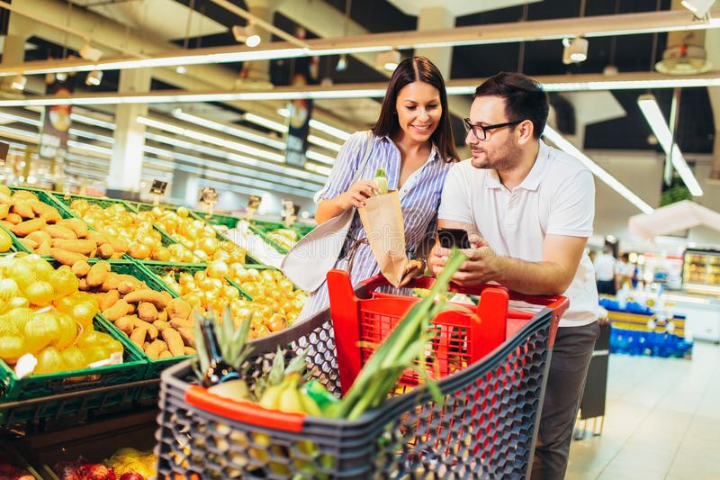 Young cheerful loving couple in supermarket with shopping trolley choosing fruits. Photo of young cheerful loving couple in supermarket with shopping trolley royalty free stock photography