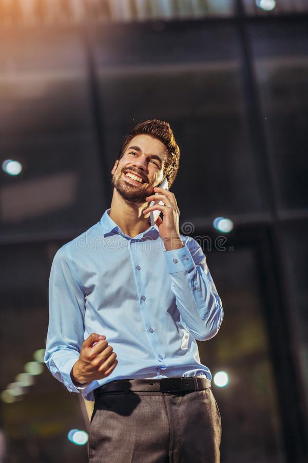 Young concentrated businessman walking outdoors on the street using mobile phone. Photo of a young concentrated businessman walking outdoors on the street using royalty free stock photo