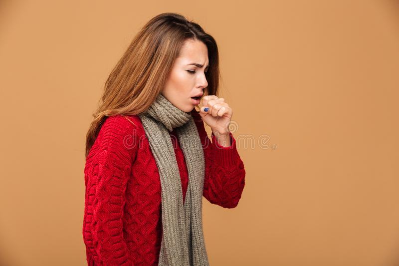 Photo of young coughing brunette woman in warm wear. Over beige background stock photo