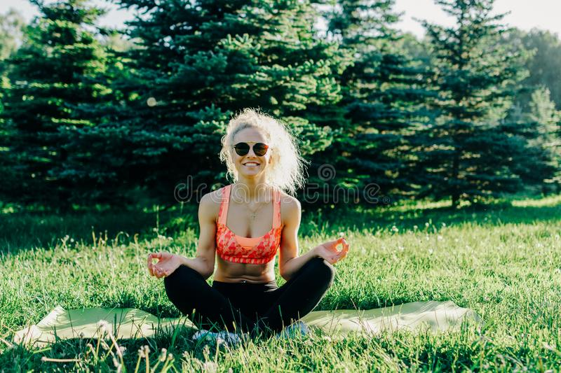Photo of young curly-haired sports woman practicing yoga on rug stock images