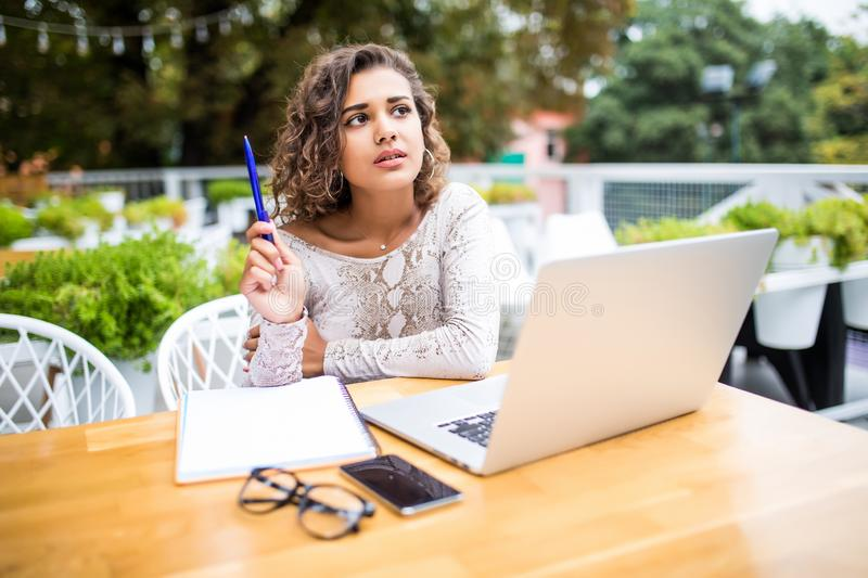 Photo of young excited latin curly woman indoors using laptop computer writing notes Looking aside have an idea in cafe stock images