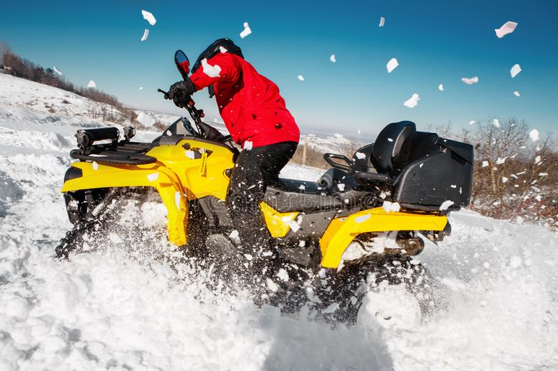 Photo of young extremal driver in red warm winter clothes and black helmet drive his ATV 4wd quad bike stand in heavy royalty free stock photography