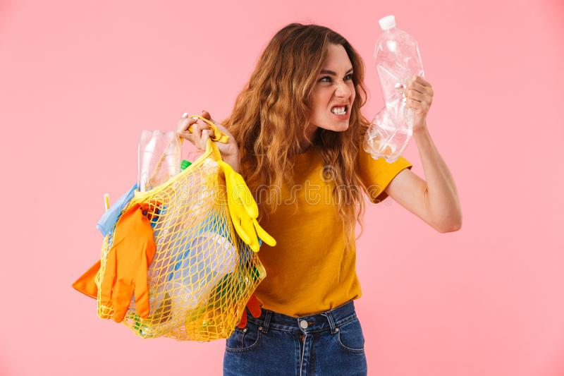 Photo of young furious woman holding bag with plastic waste and bottle royalty free stock photography