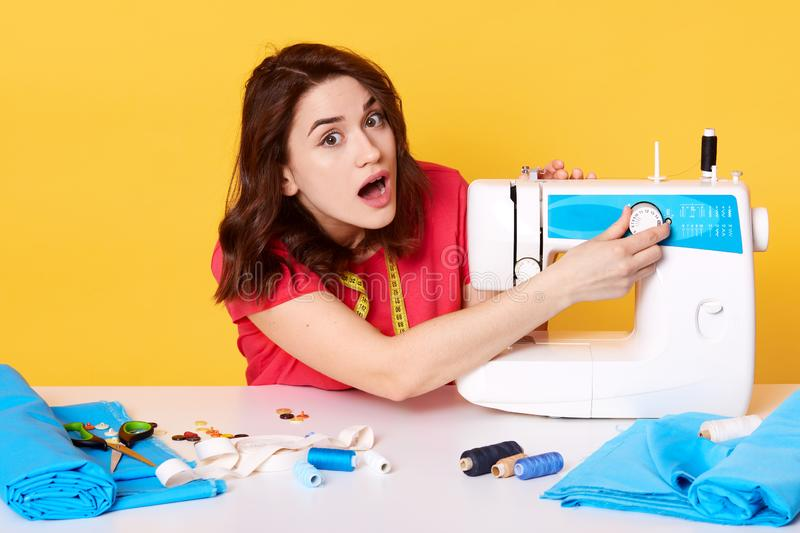 Photo of young lady works in her sewing space, has problems with sewing machine, creates accessories, repairing clothes, embroider. And packs trendy clothes royalty free stock photo