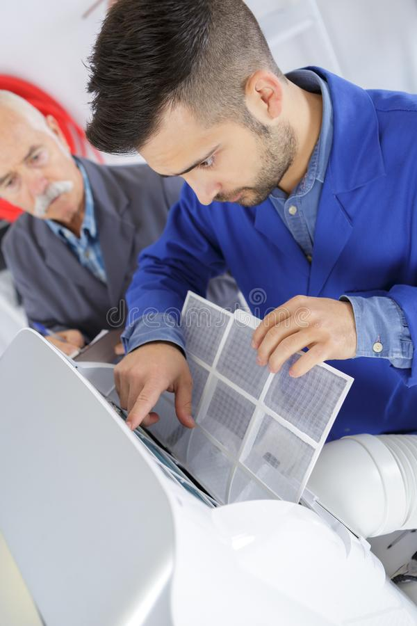 Photo young male technician repairing air conditioner royalty free stock photography