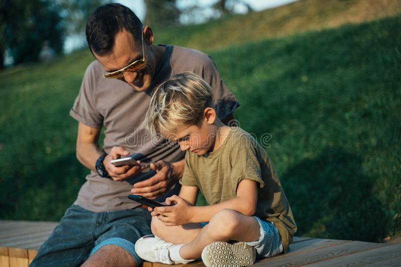 Photo of young man and boy with phones in hands sitting behind wooden fence in park stock photography
