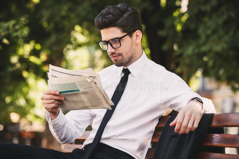 Photo of young man in businesslike suit sitting on bench in green park, and reading newspaper during sunny day. Photo of young man in businesslike suit sitting stock images