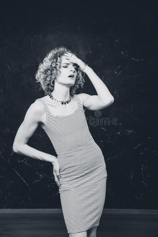 Photo of a young man in a dress stinging dress. Emotionally rolls his eyes and brings his hand to his forehead. Black and white photo of a young man in a dress royalty free stock photography