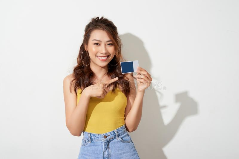 Photo of young smiling asian woman holding card royalty free stock image
