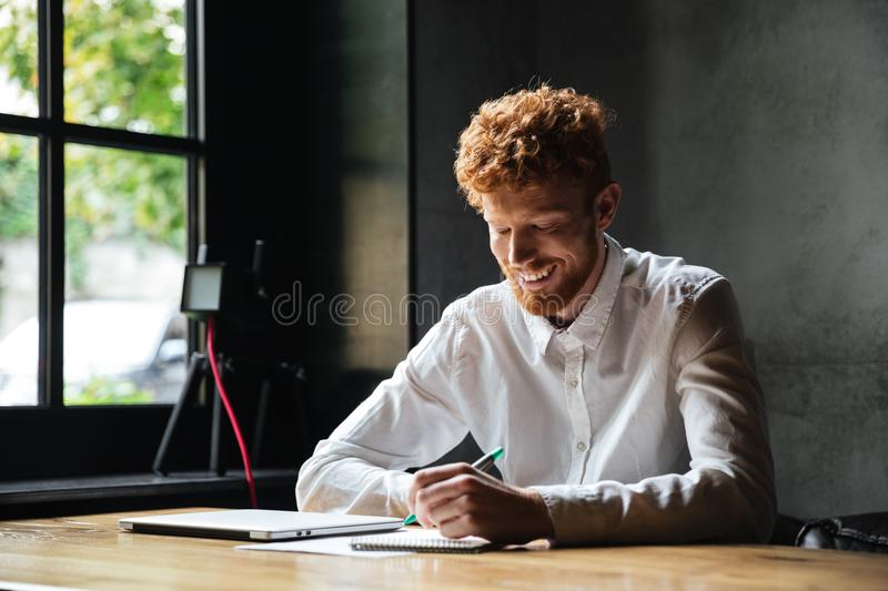 Photo of young smiling readhead bearded man, taking notes, while royalty free stock images