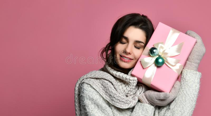 Cheerful woman in grey sweater holding gift box and having fun stock photography