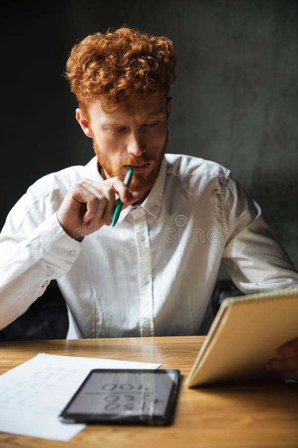 Photo of young thinking readhead bearded man in white shirt stock image