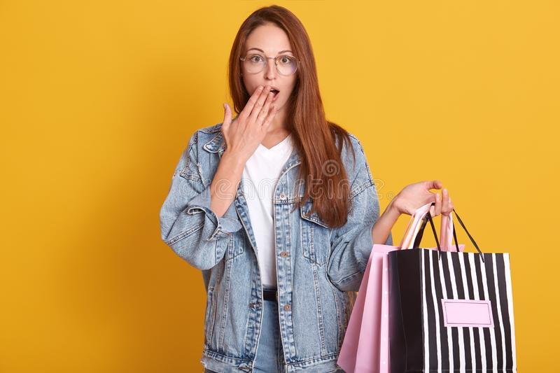 Photo of young woman in denim jacket and glasses holding shopping bags  over yellow studio background, has astonished. Facial expression, covering opened mouth royalty free stock photo