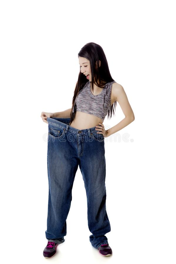 Shocked woman trying her old jeans on studio stock image