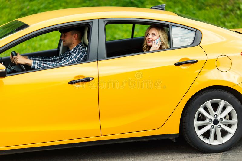 Photo of young woman talking on phone while sitting in back seat of yellow taxi with driver. Photo of young woman talking on phone while sitting in back seat of royalty free stock image