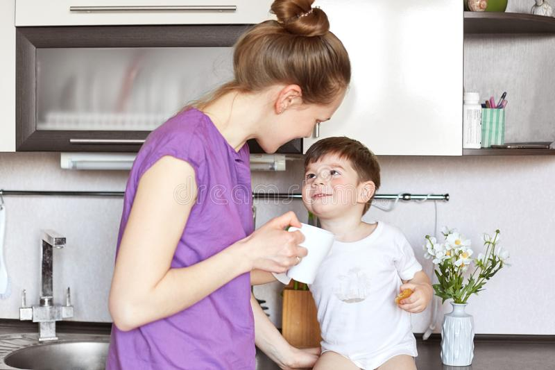 Photo of young woman in casual clothing stands against kitchen interior, looks at her adorable son with great love, gives tasty dr stock photography