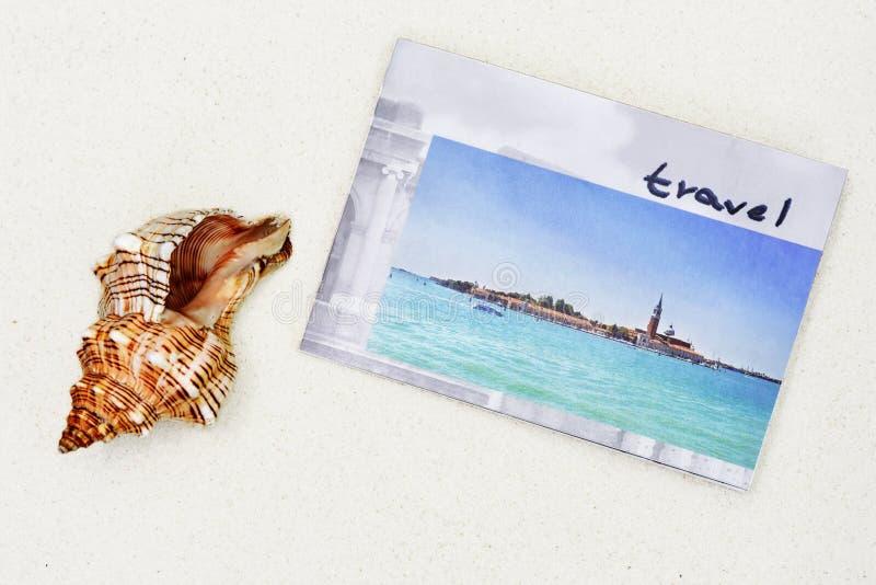 photobook和大海扇壳在白色沙子 免版税库存照片