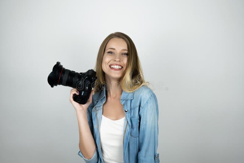 Photocamera biondo felice della tenuta della giovane donna nel suo fondo bianco isolato sorridente della mano immagine stock