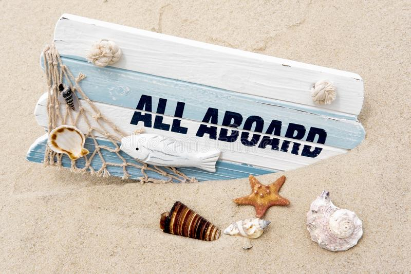 Photoconcept sea travel. Blackboard with the words all aboard, seashells in the sand. Marine photo. Travel, sailor suit stock photography