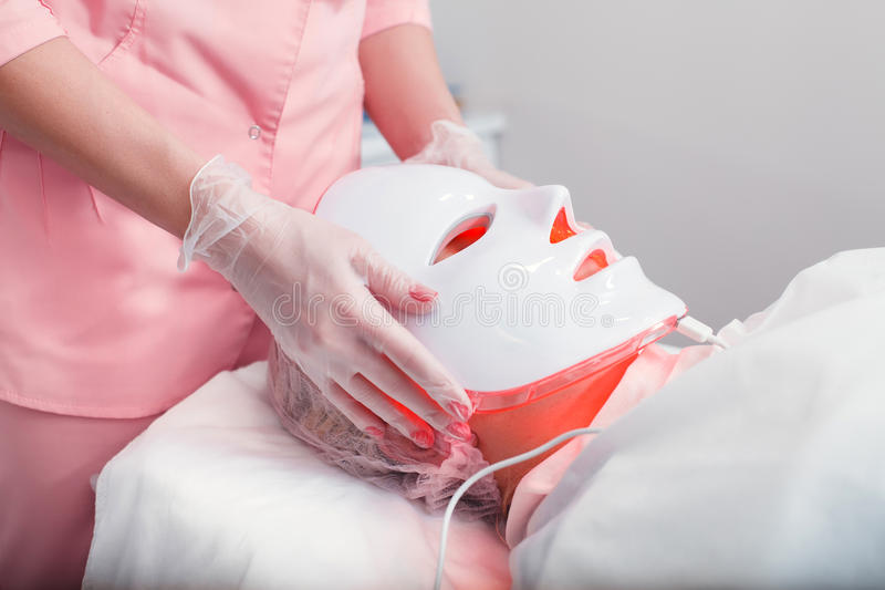 Photodynamic face mask therapy. Woman in the light photodynamic mask lying on a couch in a beauty salon. Pdt stock photography