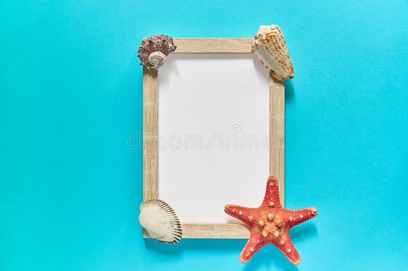 photoframe和海星顶视图与贝壳的在蓝色背景的 E 海平的位置 免版税库存照片