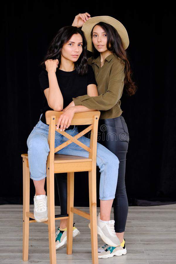 Photogenic, confident, models, girls sisters or brunette friends, looking at the camera, smiling, hugging, on a high wooden chair. The concept of fashion and stock photos