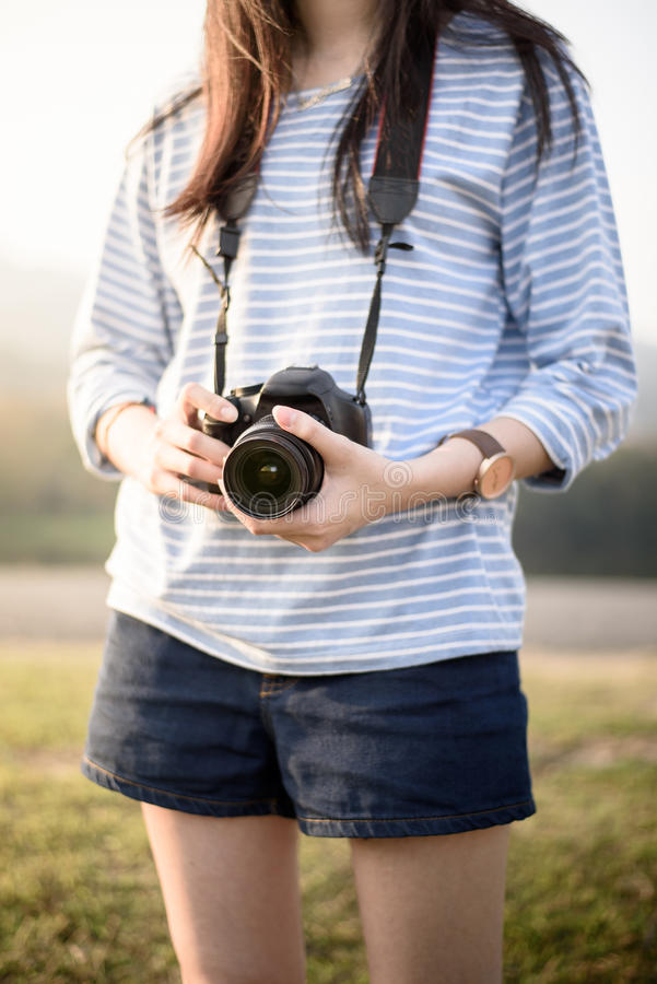 Photograher girl holds camera in garden stock photography