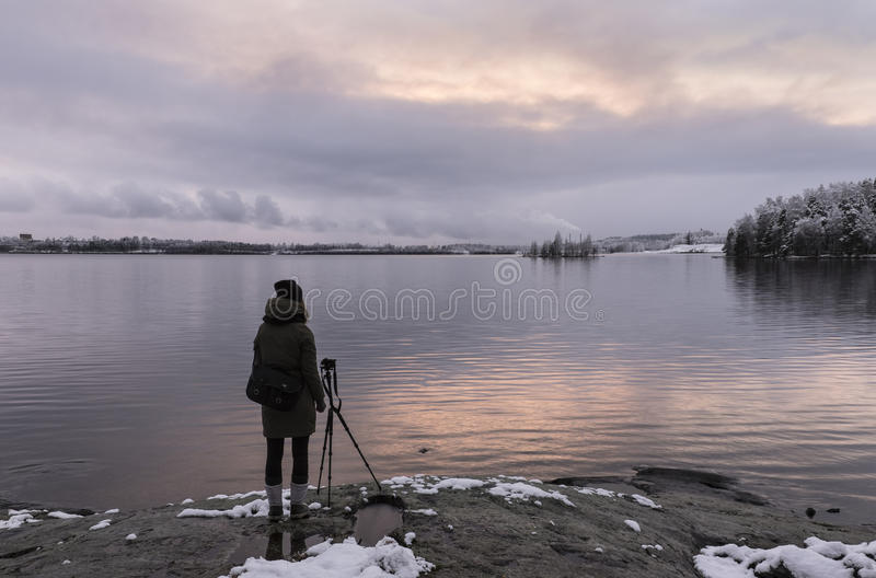 Photograpger next to lake at early winter stock photography