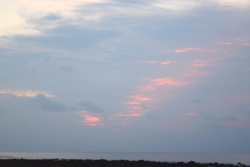Abstract Pattern of Orange Red Colors created in Morning Sky with Clouds over Ocean - Natural Background. This is a photograph of an abstract pattern of orange royalty free stock photos