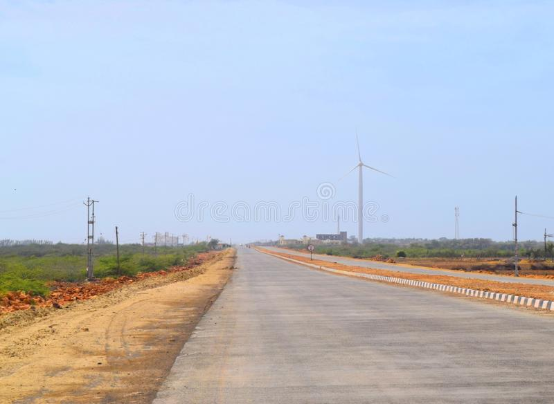 Asphalt Road in India with Roadside Windmill - Straight Highway into Far Distance - Solo Travel and Expedition royalty free stock images