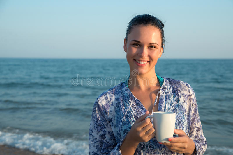 Photograph of a beautiful brunette woman with white mug with tea royalty free stock images