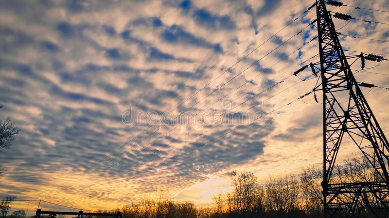 Photograph of a beautiful fabulous morning sky with cirrus clouds against the rising sun of trees and power transmission lines.  stock image