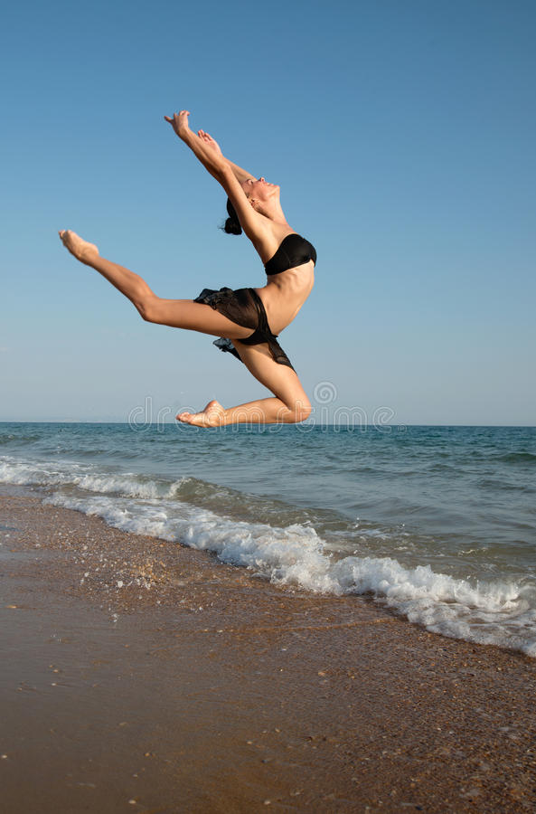 Photograph of a beautiful female dancer jumping on a beach in t. He waves of the sea. Woohoo. Enjoy life. Room for text royalty free stock image