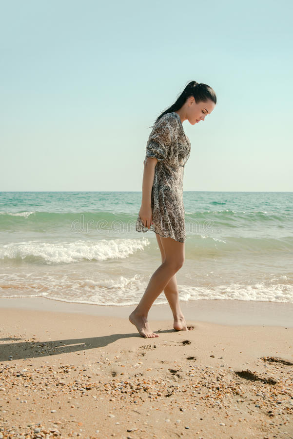 Photograph of a beautiful model relaxing on a beach in the waves stock images
