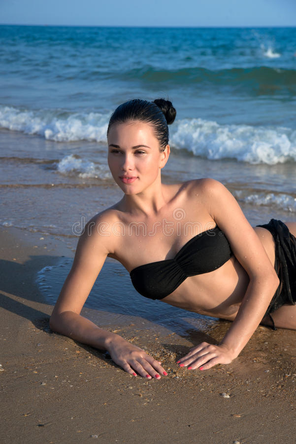 Photograph of a beautiful model relaxing on a beach in the waves stock image