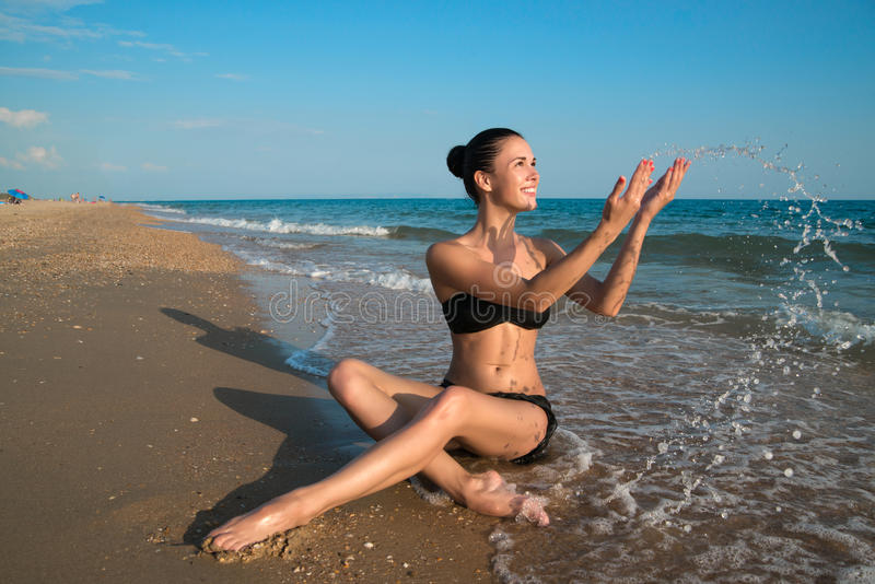 Photograph of a beautiful model relaxing on a beach in the waves stock photos