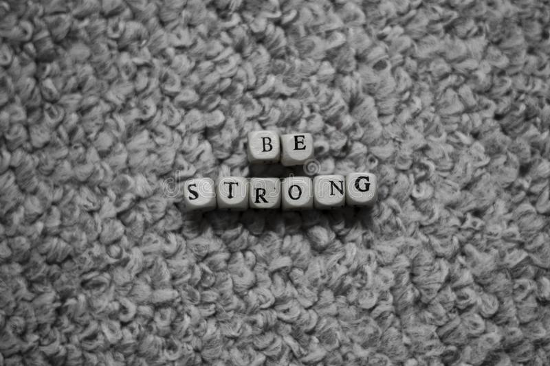 Black and white Be Strong Letters on fabric background. Photograph of Black and white Be Strong Letters on fabric background stock photography