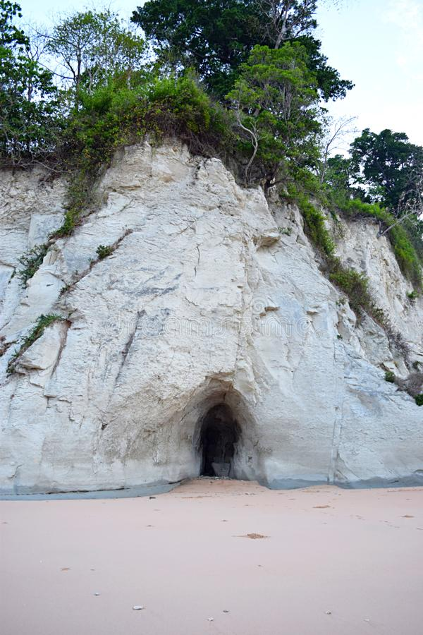 A Cave in Huge Limestone Sedimentary Cliff with Overlying Plants and Sandy Ground royalty free stock image