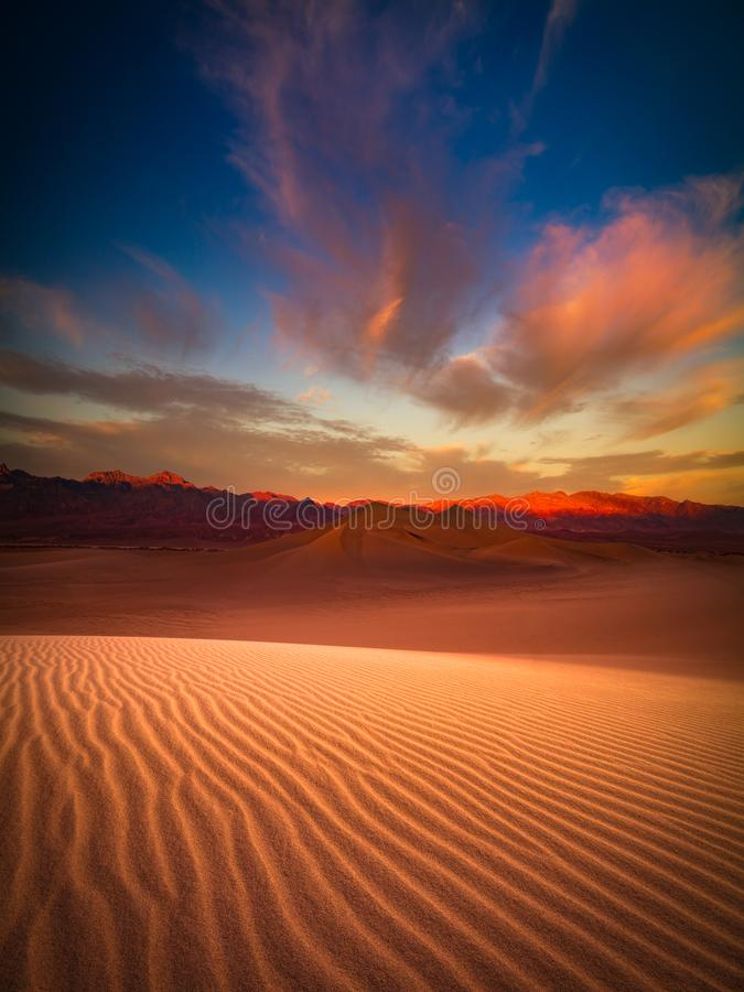 Death Valley sand dune at dusk. This is a photograph of Death Valley sand dune with colorful clouds in California, USA stock photography