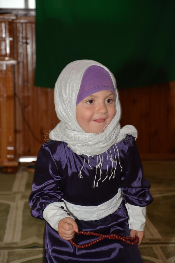 A precious Muslim child dressed in traditional Bosnian Muslim costume. Photograph of diet in the mosque, covered with religious marble, in the traditional stock photo