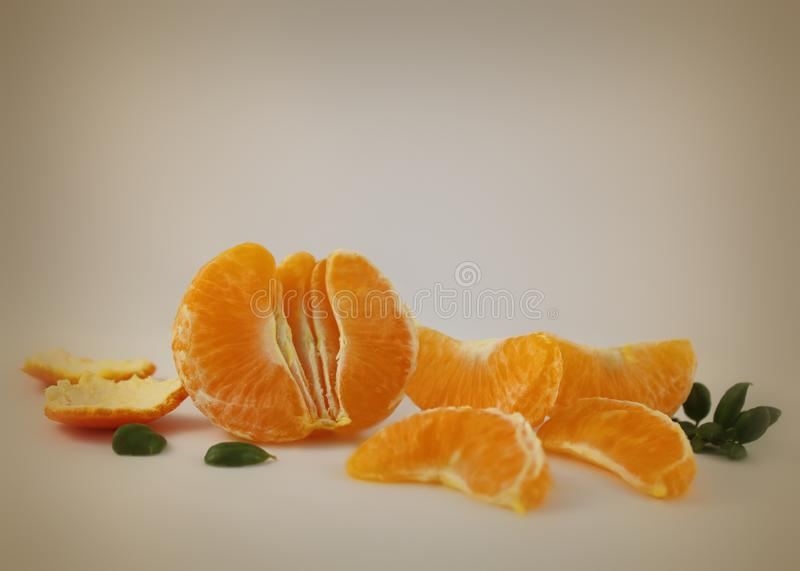 Juicy orange fruit segments surrounded with light glow on a soft tan beige background stock image