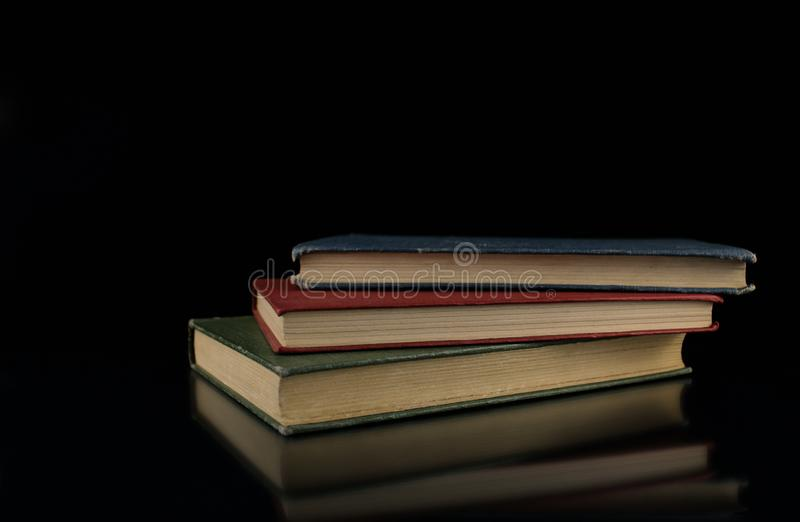 Small stack of green red blue hardcover vintage books reflecting on sleek black background royalty free stock image
