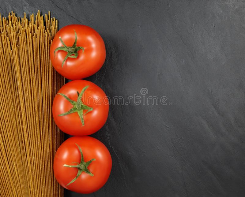 Red tomatoes aligned with uncooked whole wheat spaghetti on a dark slate gray textured background stock photos