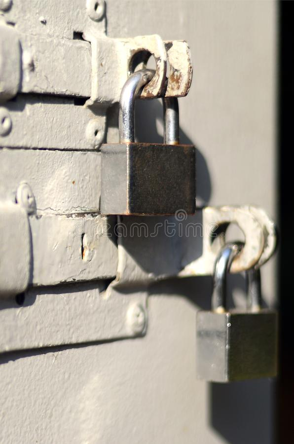 A photograph of the fragment is a metal door with two square padlocks. Selective focus with shallow depth of fiel royalty free stock photo